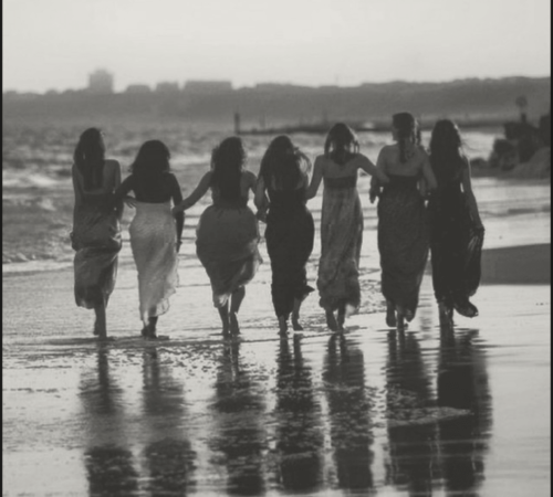 Group of women in dresses walking away on a beach while holding hands.
